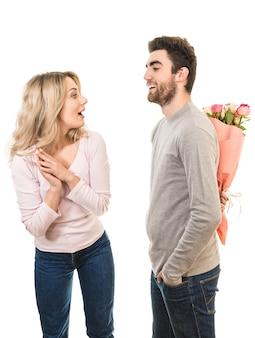 Счастливый мужчина делает сюрприз из цветов для подруги