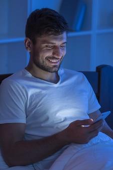 행복한 남자는 침대에 전화기를 들고 앉아 있다. 밤 시간