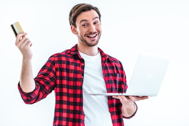 白い背景の上に立っているラップトップとクレジットカードを持つ幸せな男