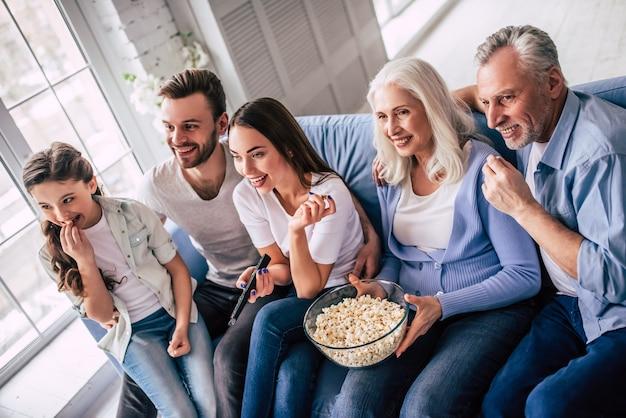 Счастливая семья из нескольких поколений смотрит телевизор