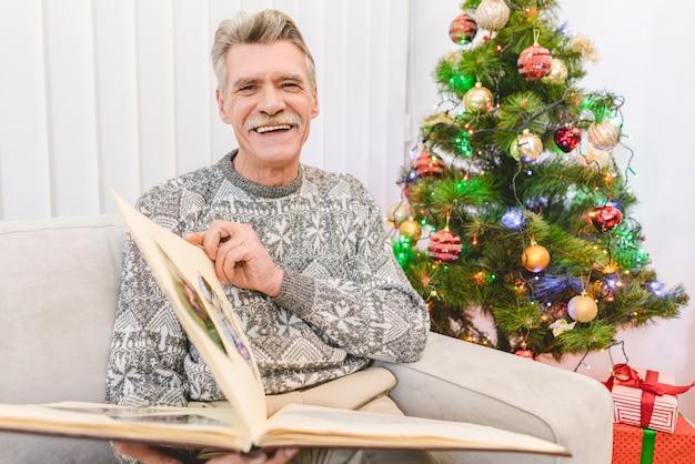 행복한 노인은 크리스마스 트리 근처에서 사진 앨범을 들고 있다
