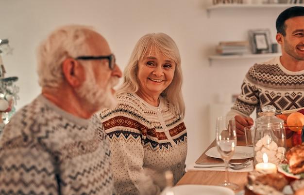 Счастливая старуха, сидящая с семьей за рождественским столом