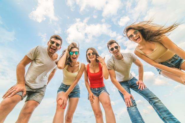 Счастливые люди смотрят в камеру на фоне облаков