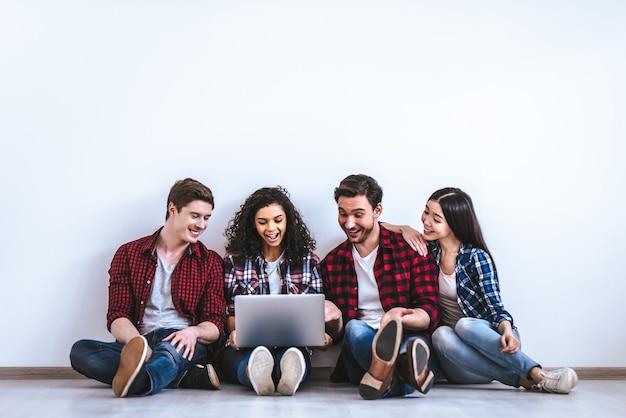 Счастливые люди с ноутбуком, сидя на белом фоне