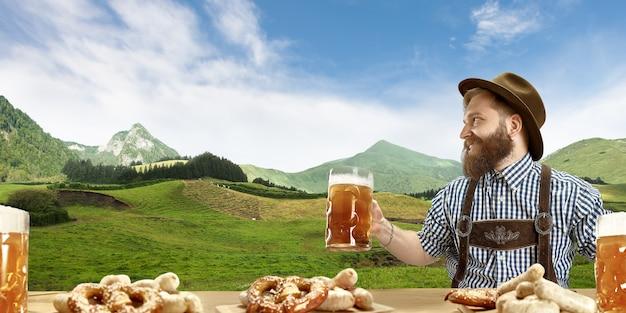 ビールのマグカップ、背景に山、広告の準備ができているチラシを保持している伝統的なオーストリアまたはバイエルンの衣装を着たビールと幸せな笑顔の男。お祝い、オクトーバーフェスト、フェスティバルのコンセプト。