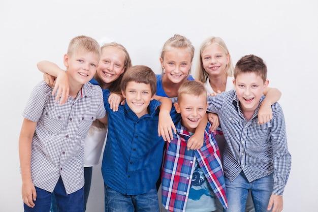 Счастливые улыбающиеся подростки на белом фоне.