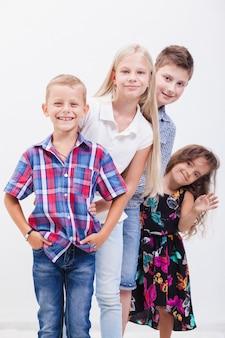 Счастливые улыбающиеся подростки стоя рука об руку на белом фоне.