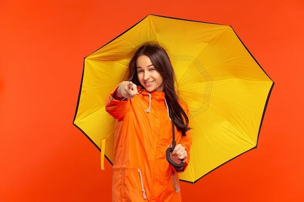 Счастливая улыбающаяся молодая девушка позирует в студии в осенней оранжевой куртке и указывает вперед, изолированную на оранжевой стене