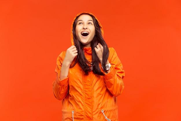 オレンジ色の壁に分離された秋のオレンジ色のジャケットのスタジオでポーズをとって幸せな笑顔の若い女の子