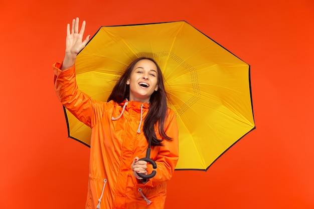 오렌지 벽에 고립 된 가을 오렌지 재킷에 스튜디오에서 포즈 행복 웃는 어린 소녀