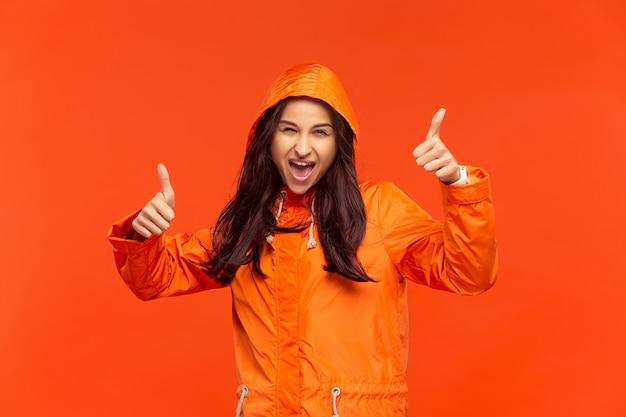 Счастливая улыбающаяся молодая девушка позирует в студии в осенней оранжевой куртке, изолированной на красном.