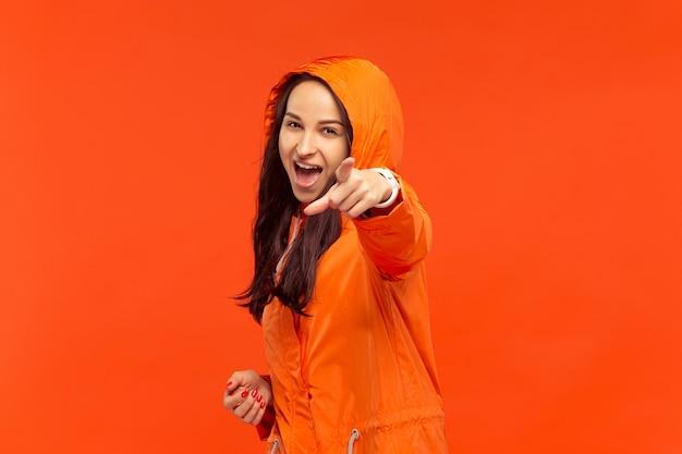 Счастливая улыбающаяся молодая девушка позирует в студии в осенней оранжевой куртке, указывая на камеру, изолированную на красном