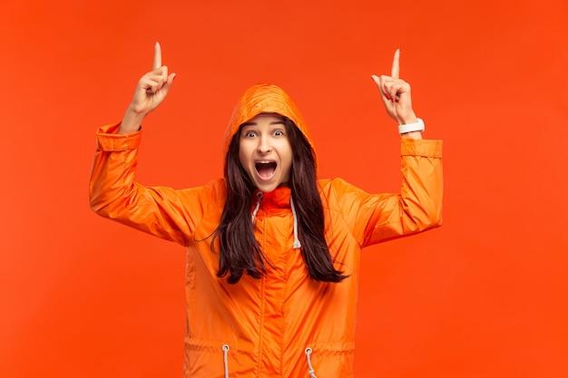 Счастливая улыбающаяся молодая девушка позирует в студии в осенней оранжевой куртке, направленной вверх изолированной на красном. положительные эмоции человека. понятие о холодной погоде