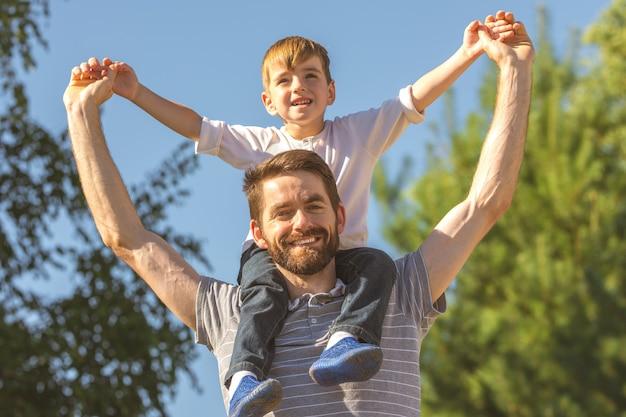 Счастливый сын сидит на шее отца
