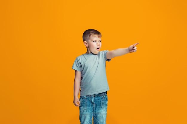 あなたを指している幸せな十代の少年、オレンジ色の背景の半分の長さのクローズアップの肖像画。