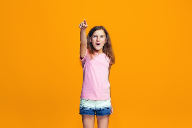 Счастливый подросток девушка указывая на вас, половинной длины крупным планом портрет на оранжевом фоне.