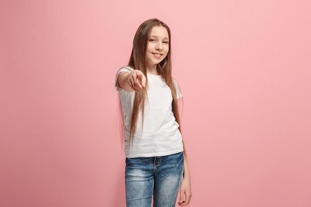 ピンクの壁に半分の長さのクローズアップの肖像画を指している幸せな十代の少女