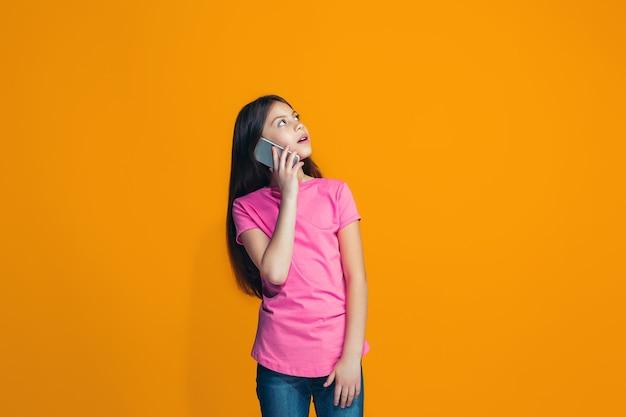 Счастливая девушка-подросток стоя и улыбается против апельсина.
