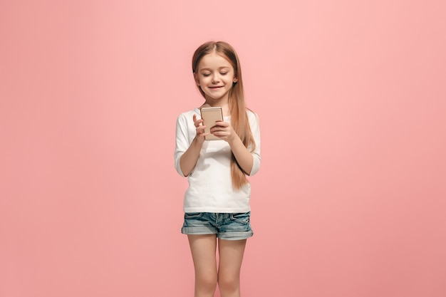 분홍색 벽에 서서 웃고 행복 십대 소녀