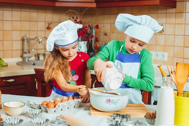幸せな2人の面白い子供が生地を準備し、キッチンでクッキーを焼く