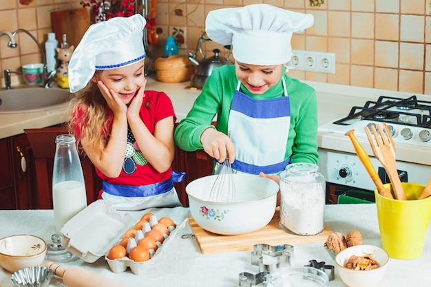 Счастливые двое веселых детишек готовят тесто, пекут печенье на кухне