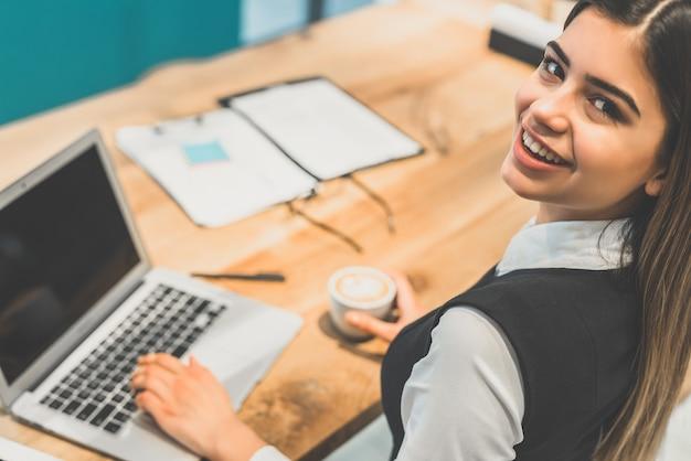 Счастливая женщина пьет кофе и работает с ноутбуком