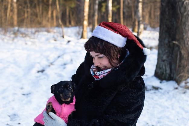 犬と冬の自然の中で幸せな女性