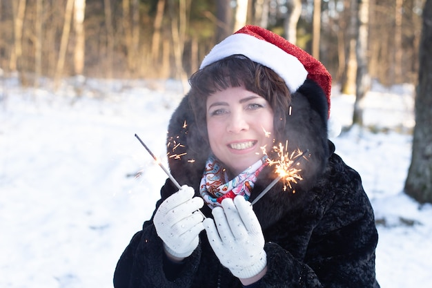 線香花火、クリスマスと冬の自然の中で幸せな女性