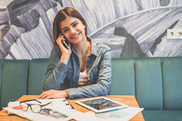 카페 테이블에서 행복한 여자 전화