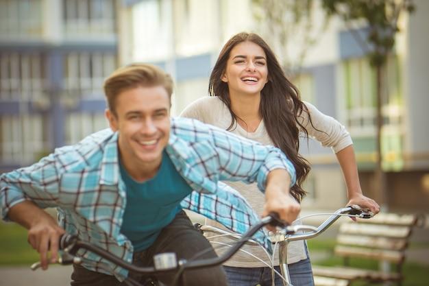 幸せな女性は男の近くに自転車で立っています
