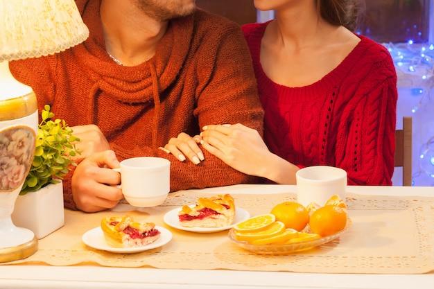 Счастливая молодая пара с чашками чая и пирожными.