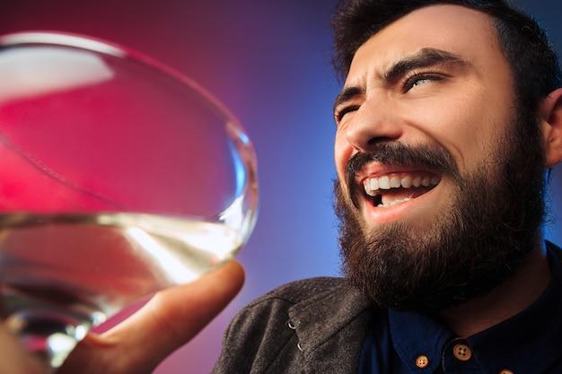 ワインのグラスでポーズをとって幸せな若い男。感情的な男性の顔。ガラスからの眺め。パーティー、クリスマス、アルコール、お祝いイベントのコンセプト
