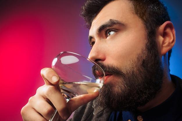 ワインのグラスでポーズをとって幸せな若い男。