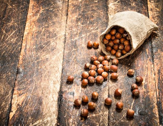 古い袋に入ったヘーゼルナッツ。木製の背景に。