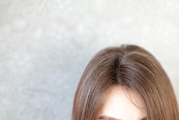 Голова женщины с пробором седых волос. женщина делает прическу. каштановые волосы на крупном плане головы женщины.
