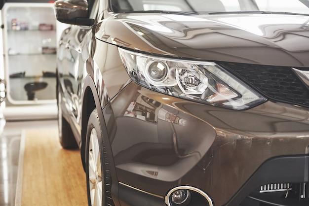 Фары и капот роскошного черного автомобиля.