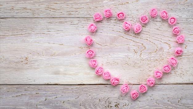 Сердце из маленьких искусственных розовых роз на светлом деревянном деревенском фоне, вид сверху