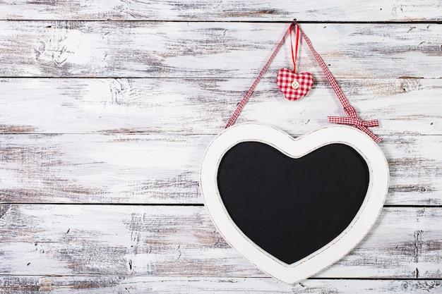 Классная доска в форме сердца на ветхом деревянном фоне