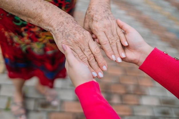 Руки помощи по уходу за престарелыми на дому в парке под открытым небом.