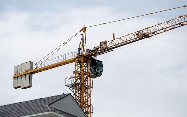 高層タワークレーンは、市街地近くの建設現場の建物の上で、コピースペースのある正面図で作業しています。