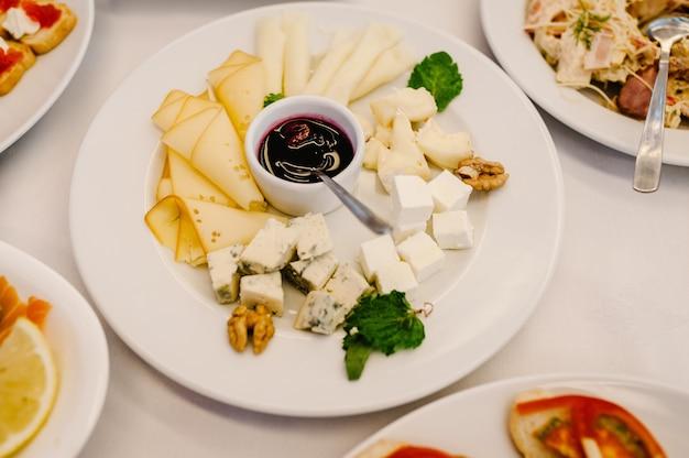 Праздничный стол с закусками из сыра, мясными закусками. сервированный стол с едой. праздничный стол. свадебный стол, еда.