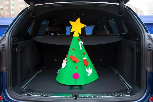휴일이 다가오고 있습니다. 장난감과 별이 장식된 펠트 크리스마스 트리가 현대식 크로스오버의 빈 트렁크 중앙에 서 있습니다. 클로즈업, 소프트 포커스