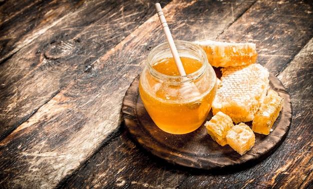 나무 테이블에 견과류와 함께 항아리에 꿀.