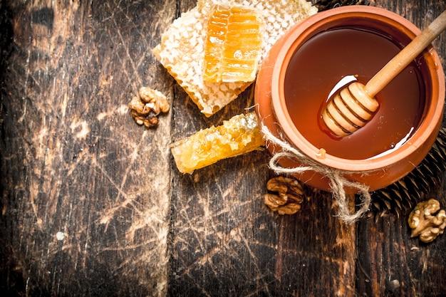 ナッツとコーンが入った鍋の中の蜂蜜。木製の背景に。