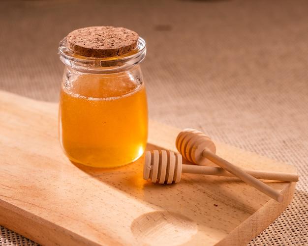 꿀 숟가락 근처 나무 보드에 꿀 항아리