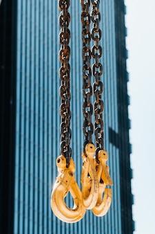 Крюки автокрана у стекла высоких зданий. множество крюков, подвешенных на цепях, подвешенных к крану.
