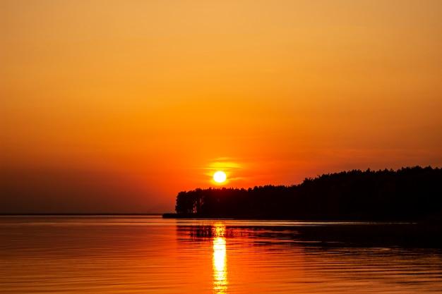 Горизонтальное фото золотого заката над рекой или морем. отражение в воде подобно огню. берег моря.