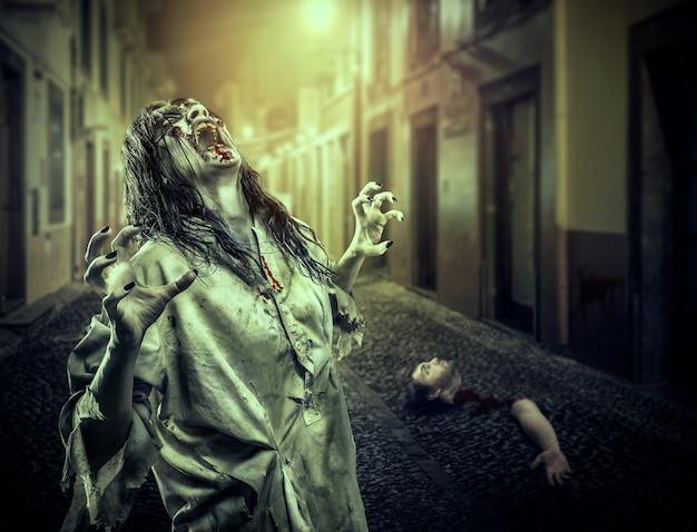 暗い通りでゾンビの女の子を叫ぶ恐怖。吸血鬼。ハロウィーン。