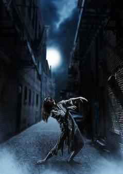 月に対して暗い通りにいるホラーゾンビの女性。ハロウィーン。怖い。