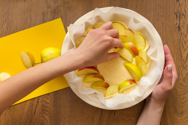 집의 여주인이 부엌에서 사과 샬롯을 준비하고 있습니다. 사과 파이에 재료를 넣습니다 프리미엄 사진